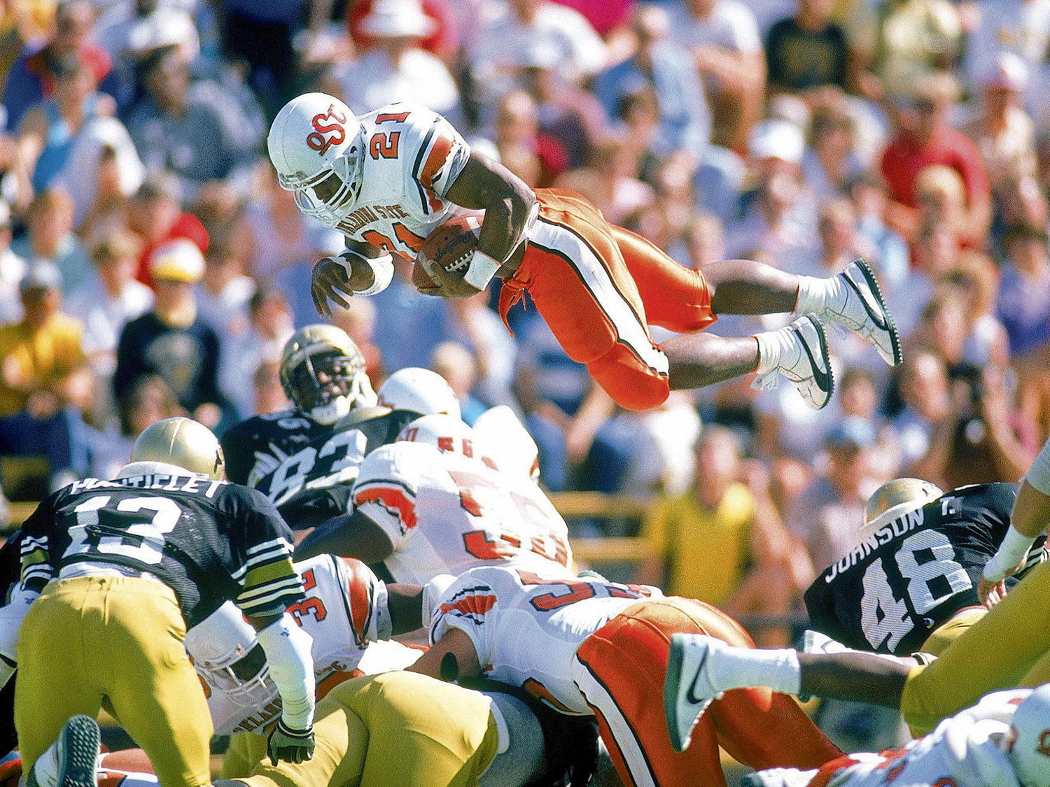 Heisman Trophy winner Barry Sanders flies over the defense of Colorado for a TD.
