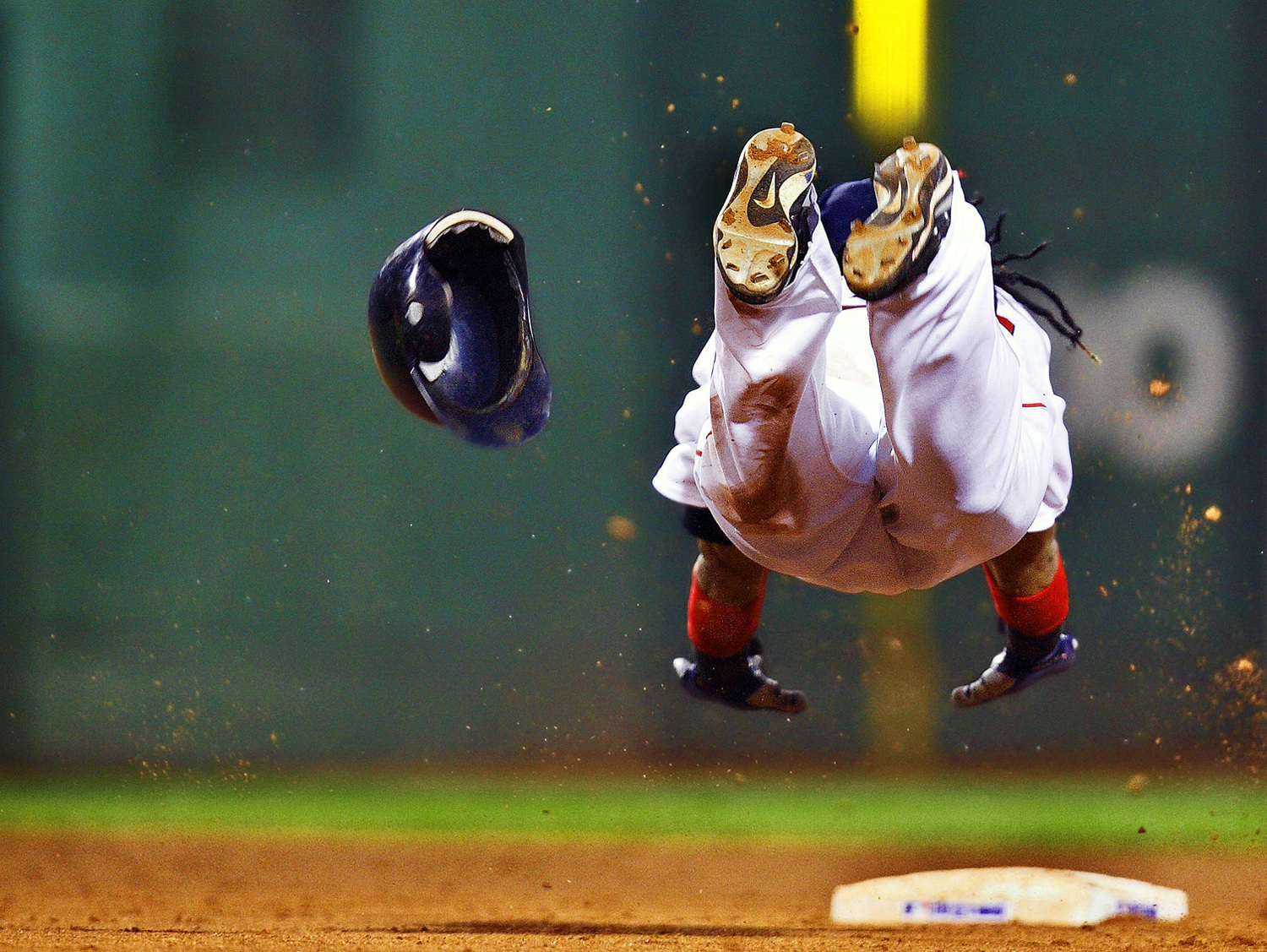 Manny Ramirez of the Boston Red Sox slides head first with his helmet flying off.