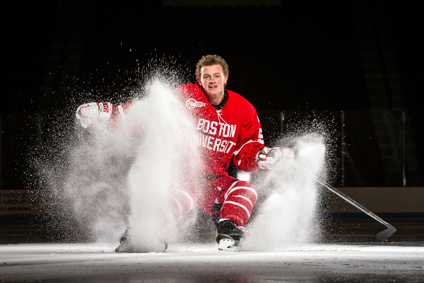 Boston University hockey player Jack Eichel hockey stops  spray for a portrait.