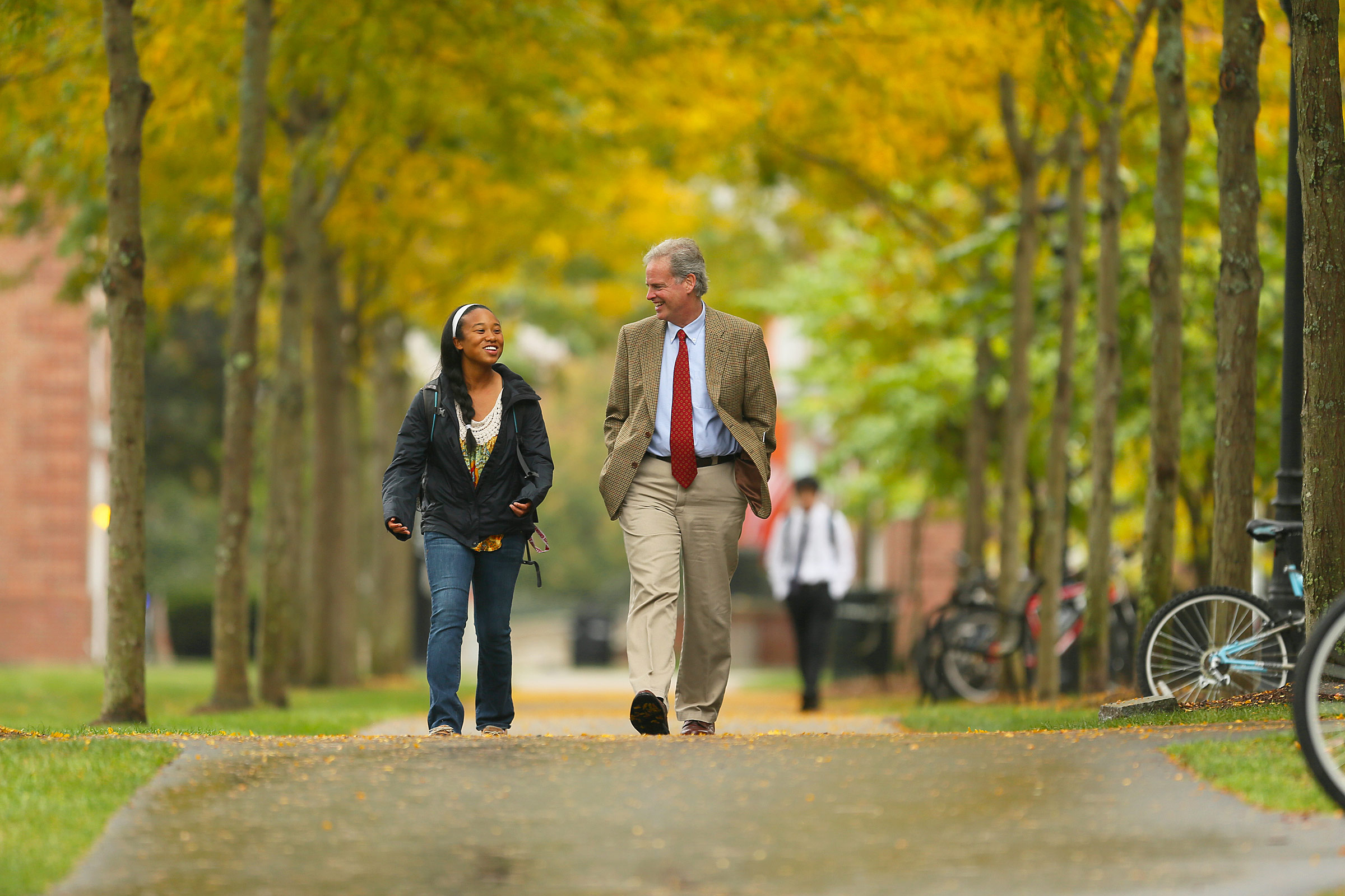 Fall colors are out as Phillips Exeter principal Thomas Hassan walks with a student.