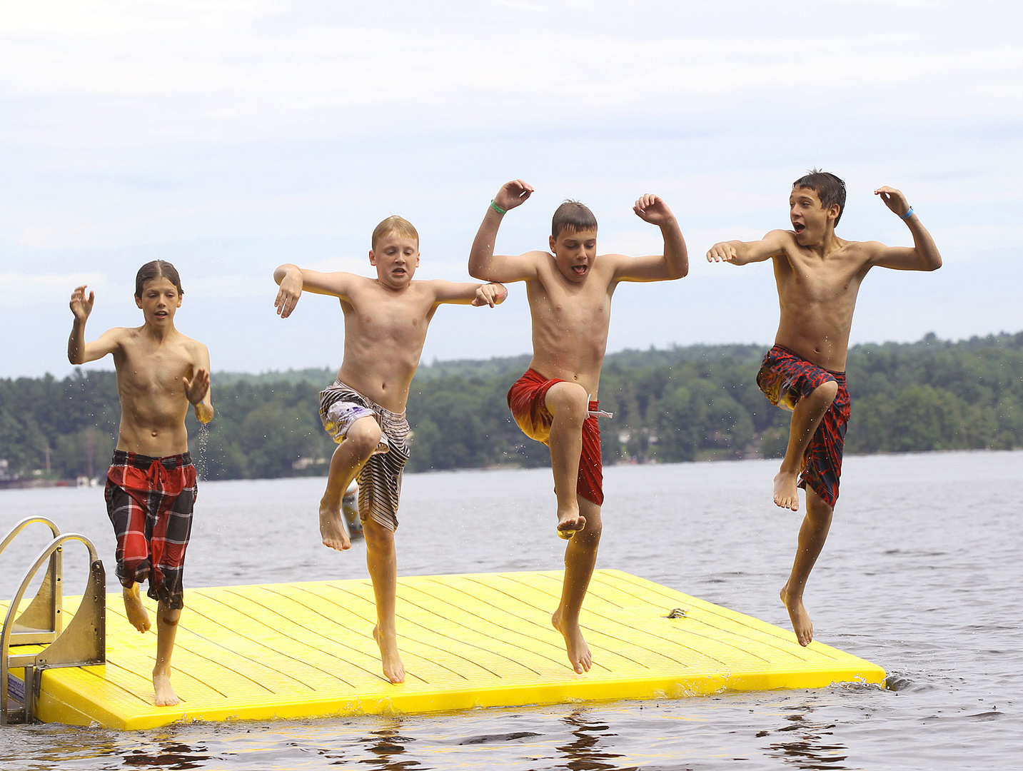 Campers at the YMCA Camp of Maine dive into a lake for a swim.