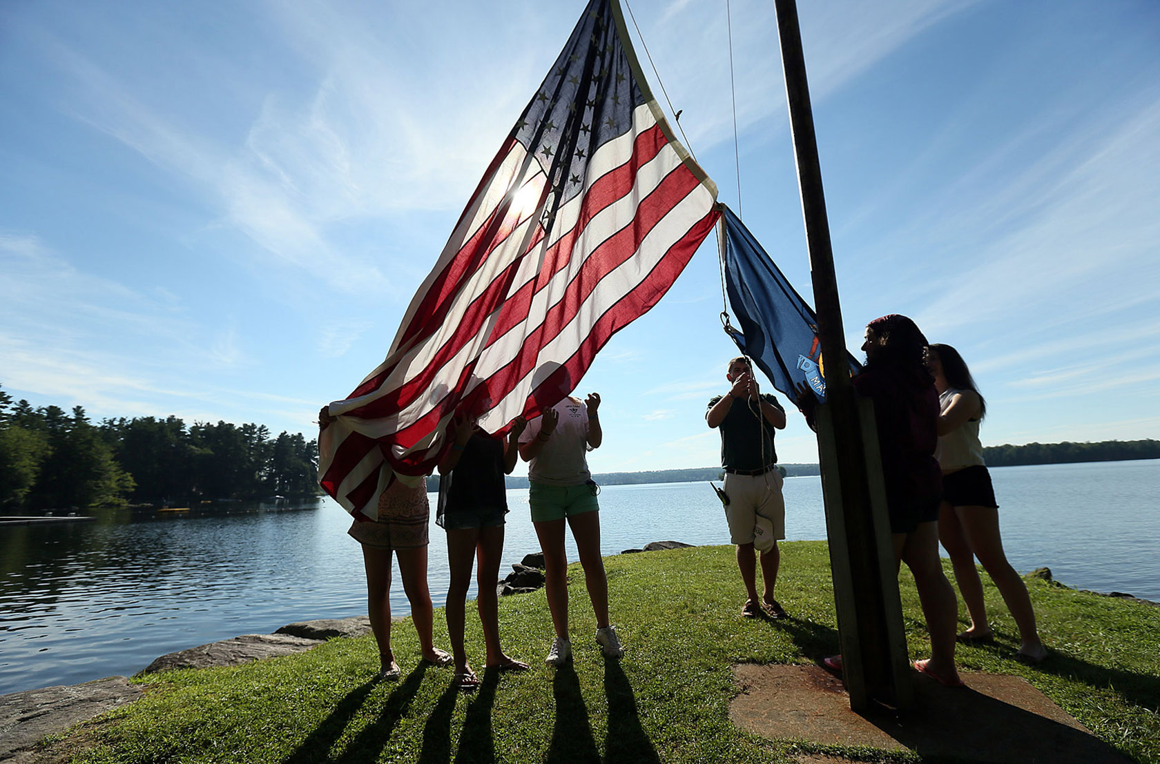 Old Glory is raised for the day at a YMCA Camp in Winthrop, Maine