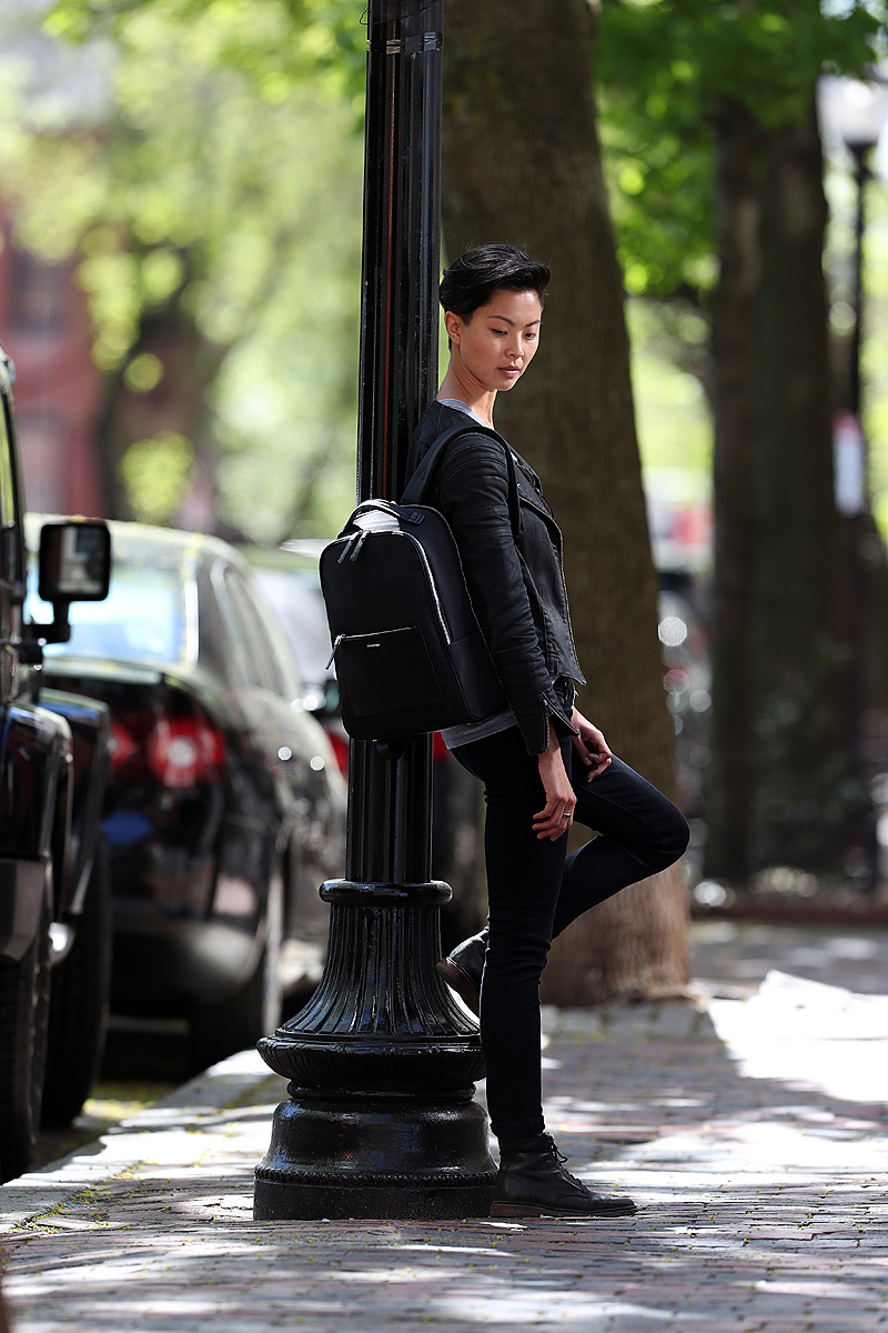 Celebrity chef Kristen Kish is shown with her backpack on a tree lined street.