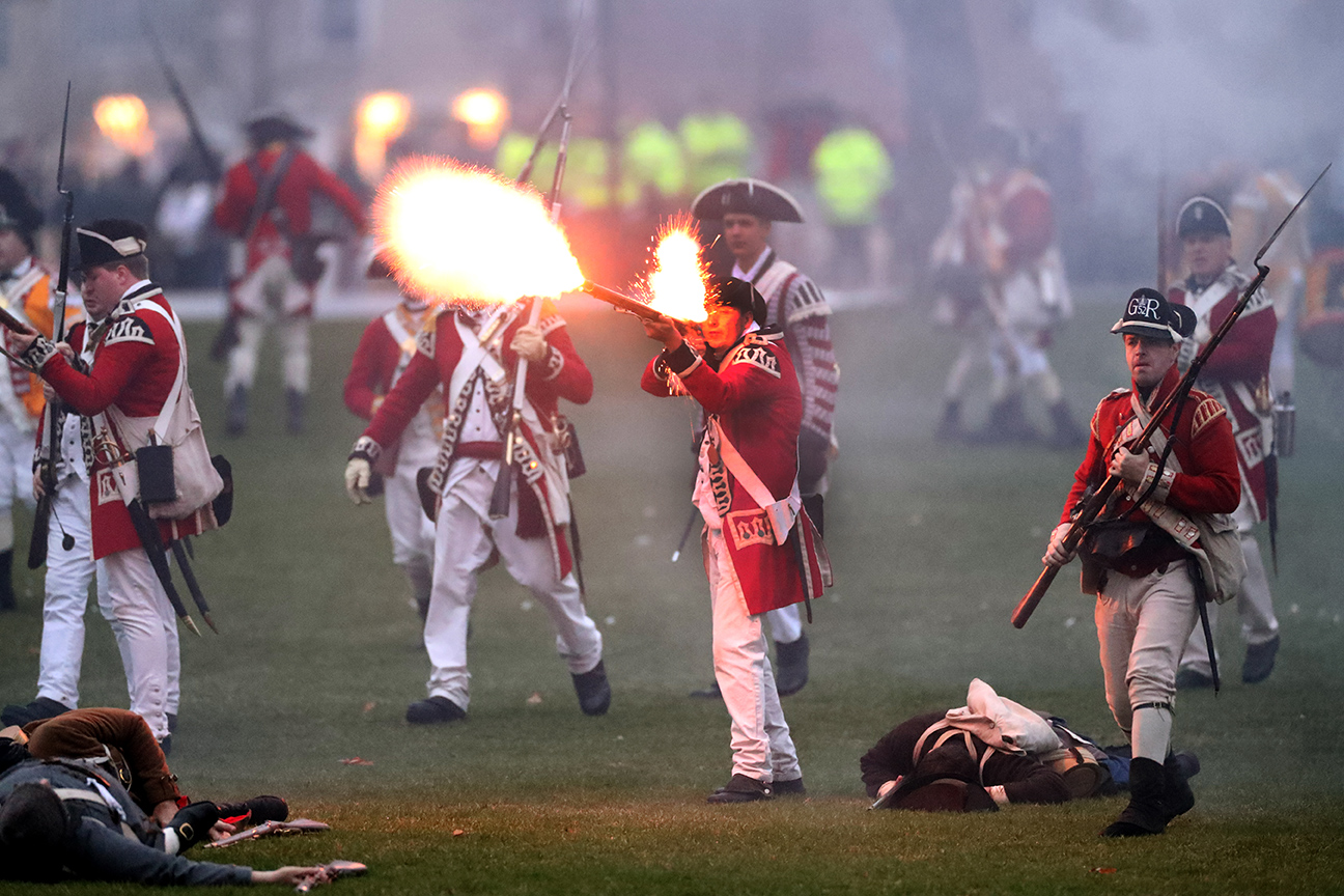 British soldiers fire on colonists as part of the reenactment of the start of the Revolutionary War in Lexington, MA.