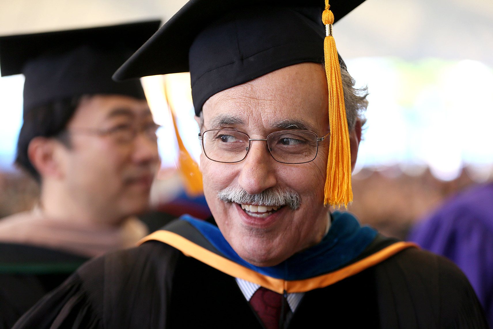 A Suffolk University professor in cap and gown marches into graduation services.