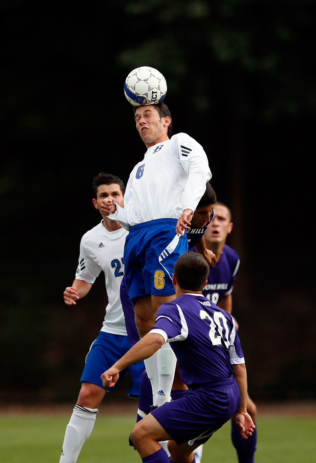 A Bentley University player heads a ball in a mens soccer competition against Stonehill College.