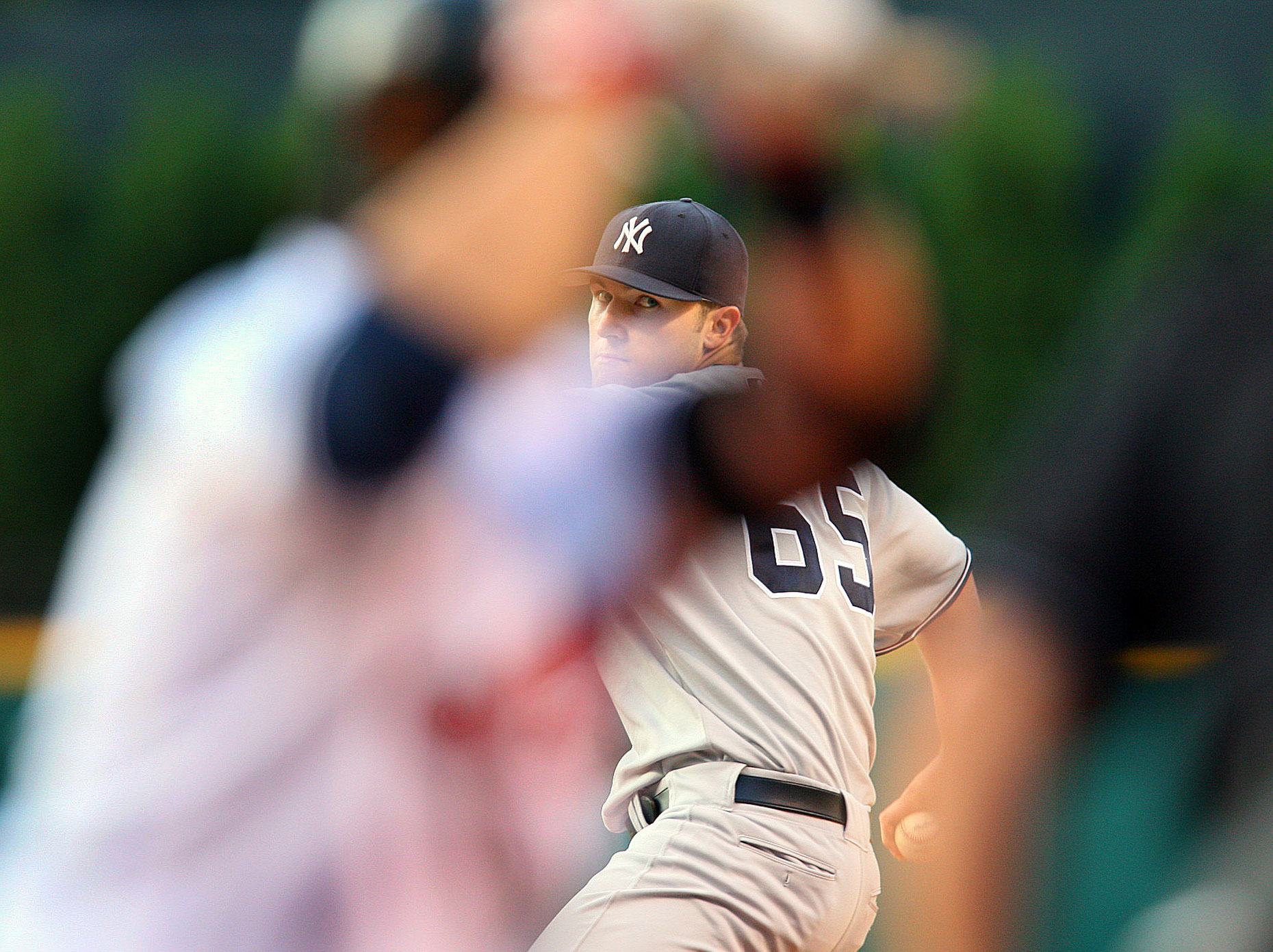 Yankee pitcher Phillip Hughes is framed by the batter during a game in Cleveland.