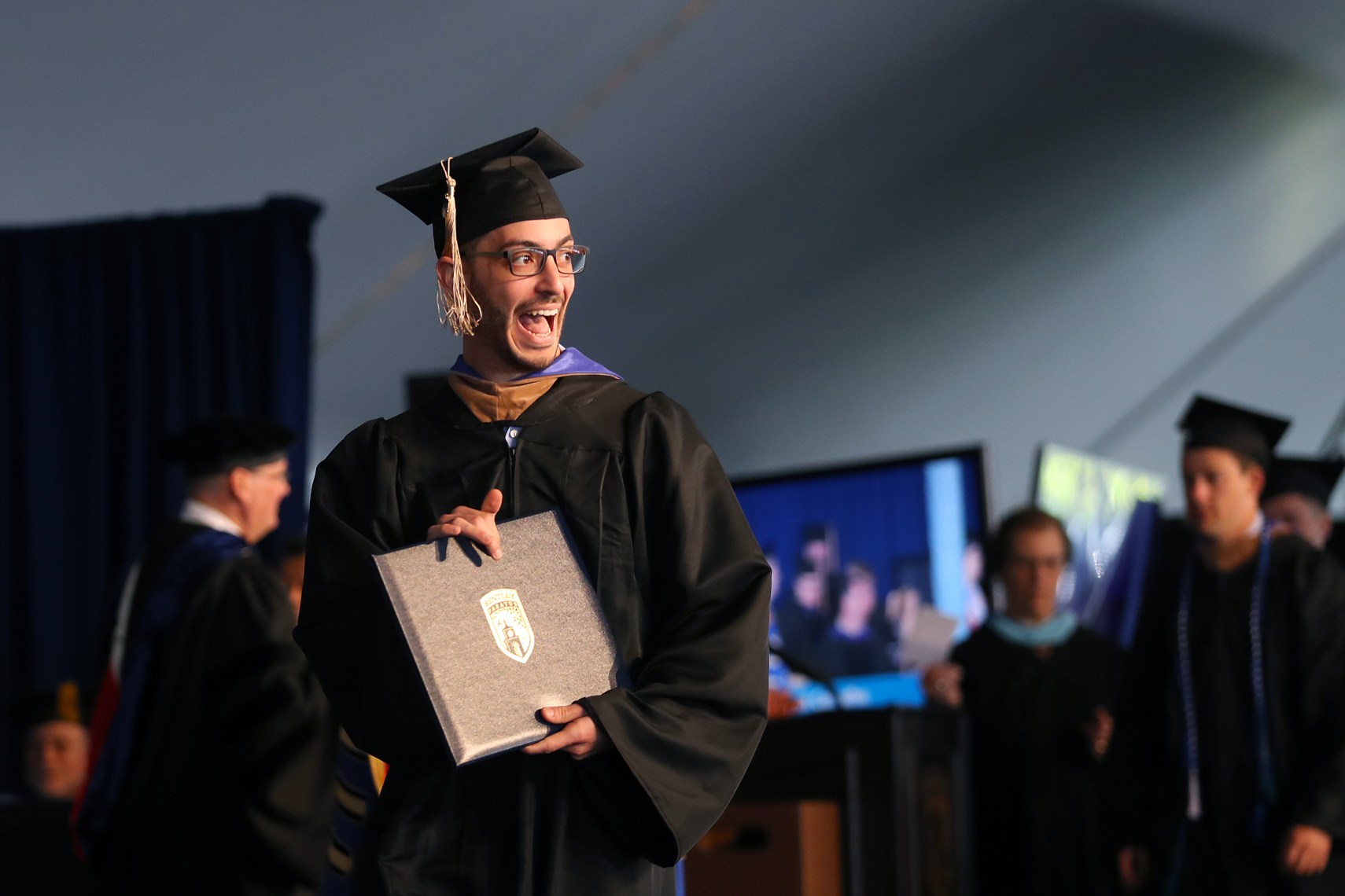 A  recent Bentley graduate shows off his diploma during graduation exercises.