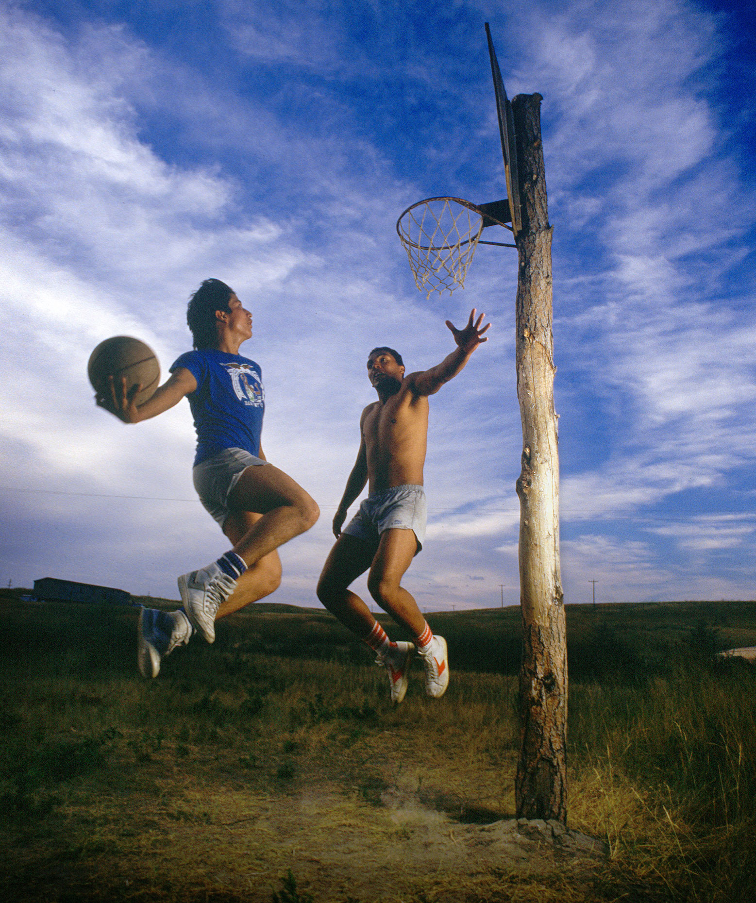 Two native American basketball players use a hoop nailed to a tree to play.