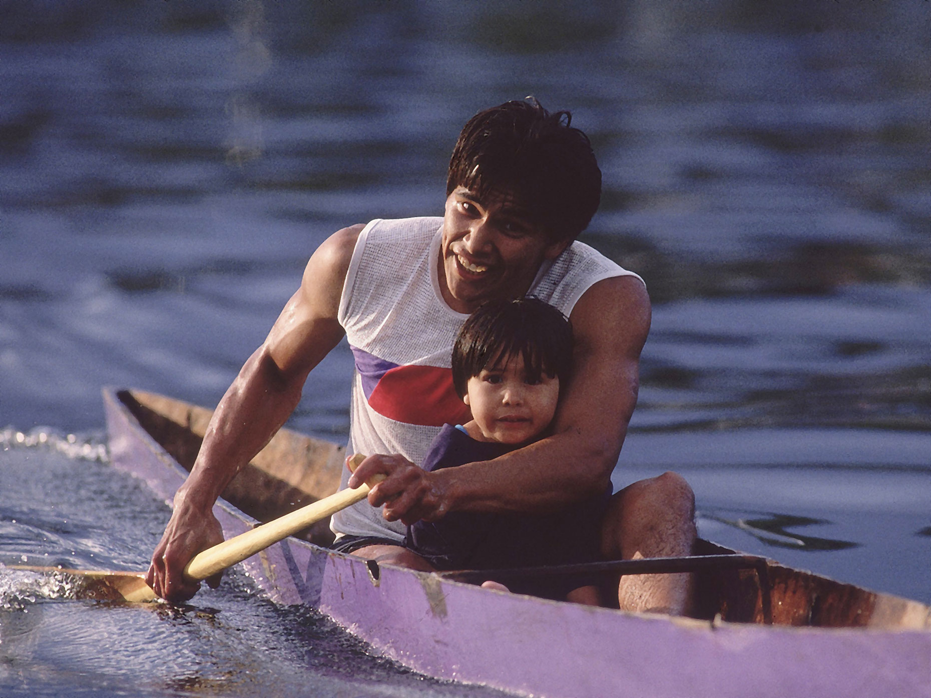 A father rows a canoe with his son on the Lummi Indian Reservation.