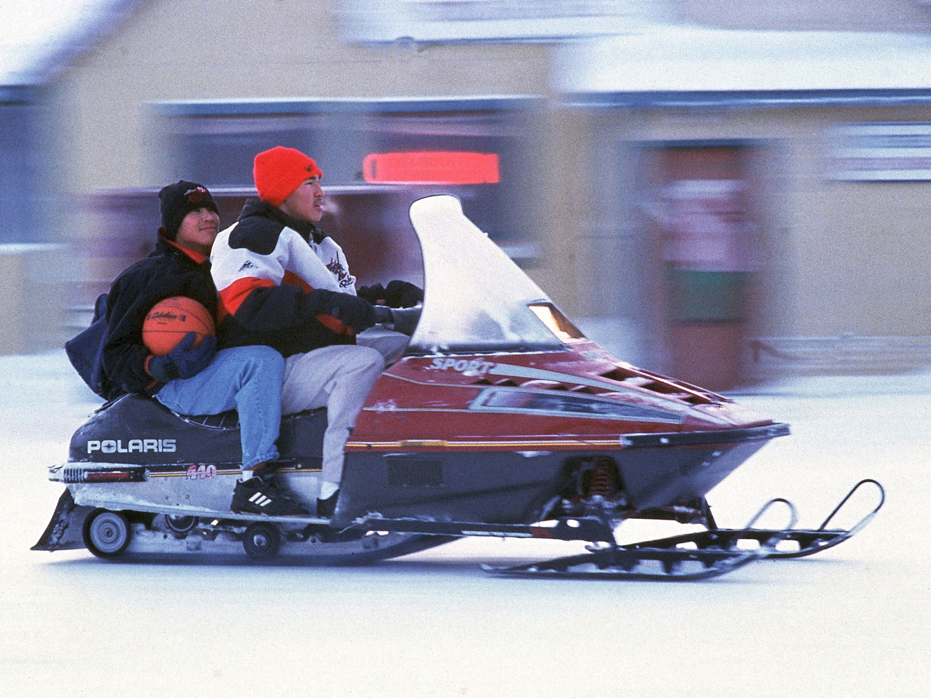 Basketball players head to practice on a snowmobile in Kotzebue, Alaska.