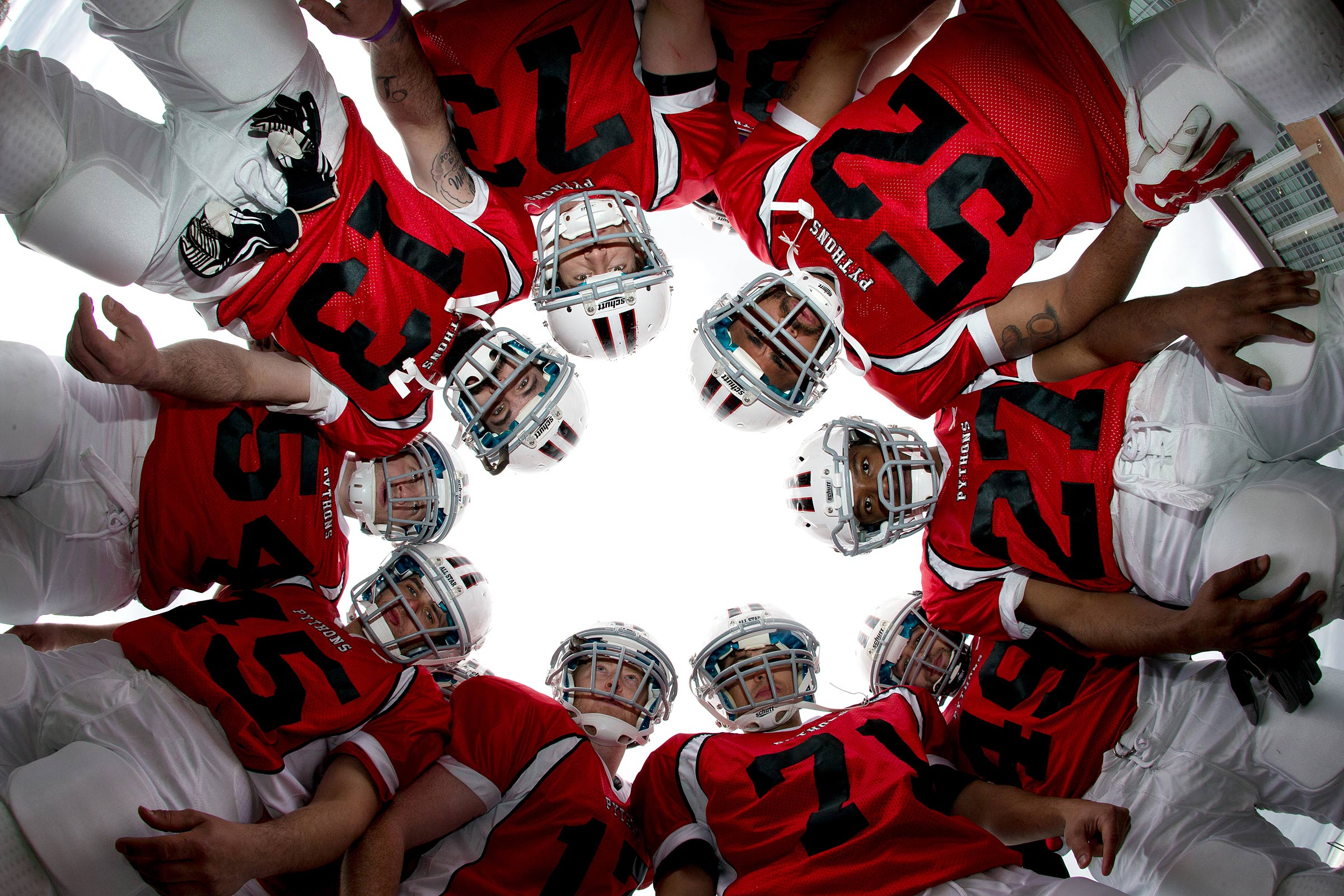 A low angle  view from inside the huddle showing the team from below.