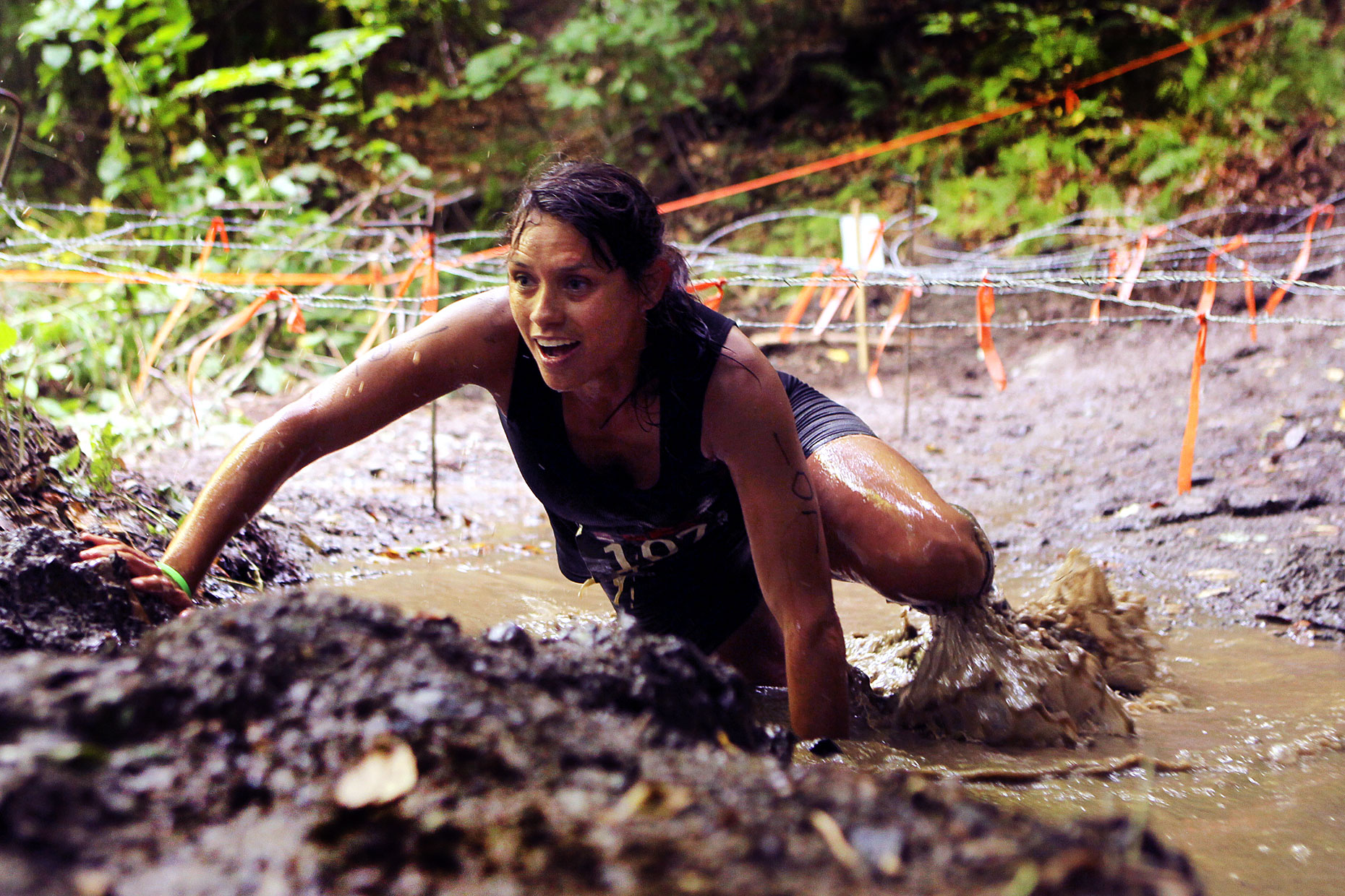 A participant in the Bone Frog challenge competition climbs a muddy slope.
