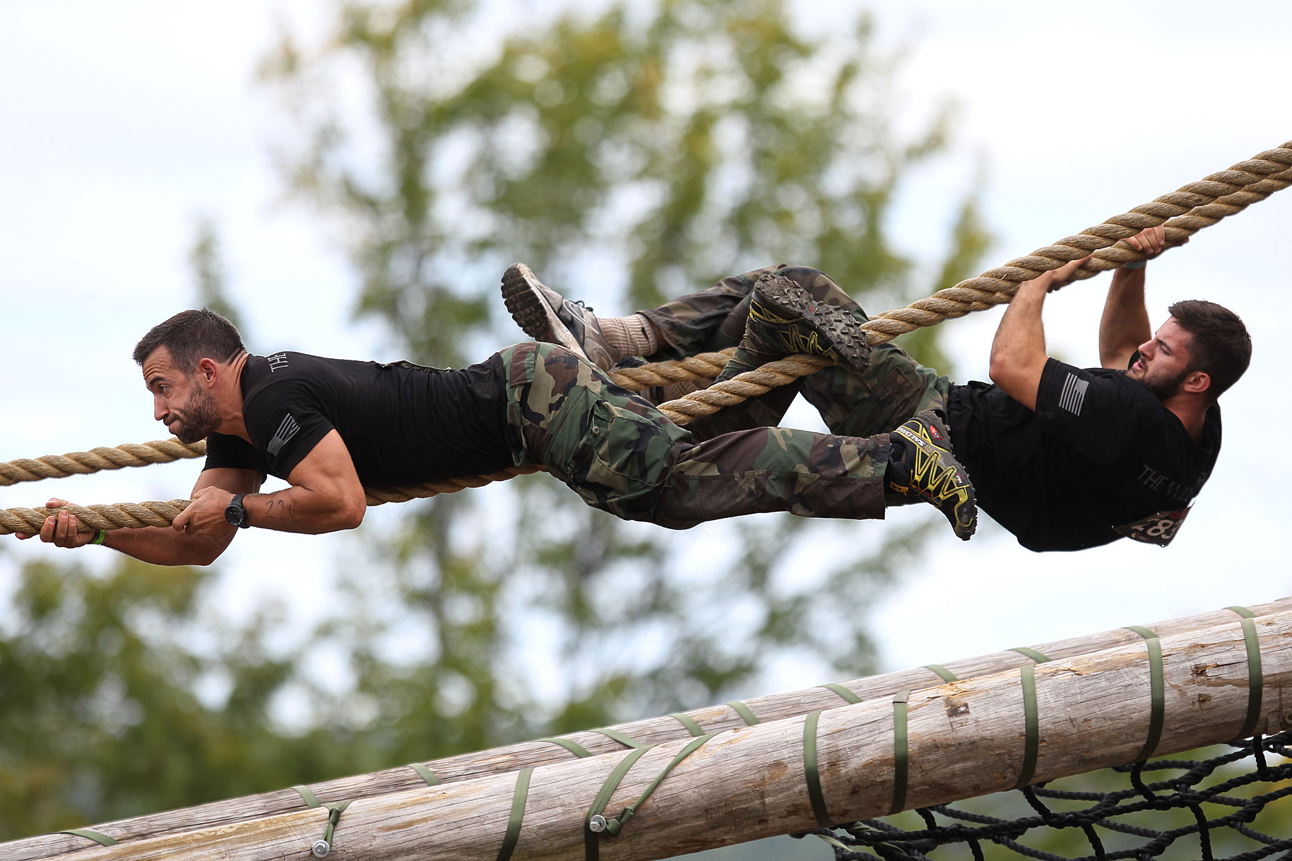 Competitors climb on a rope as part of an adventure competition.