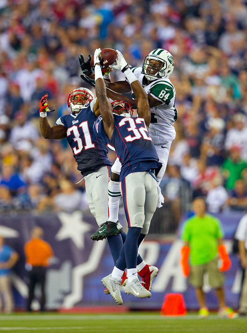 Jets receiver Stephen Hill battles New England defenders Devin McCourty and Aqib Talib for a pass.