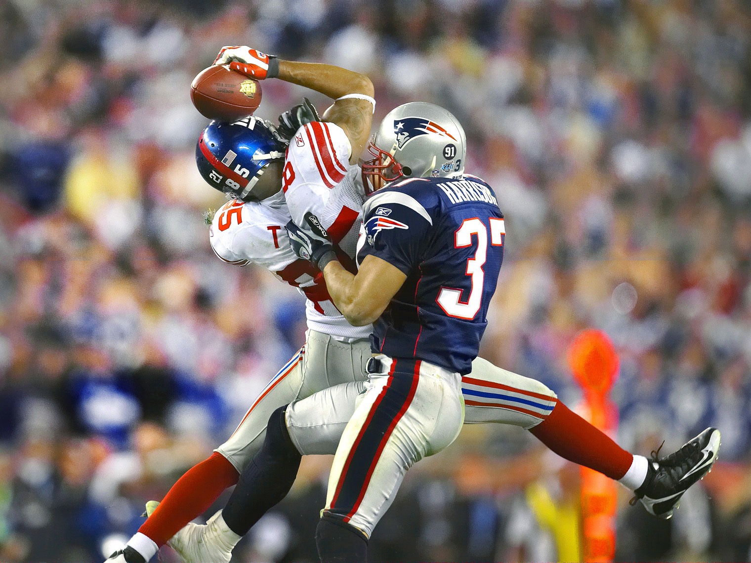 NY Giants receiver David Tyree makes a catch by trapping the ball on his helmet.